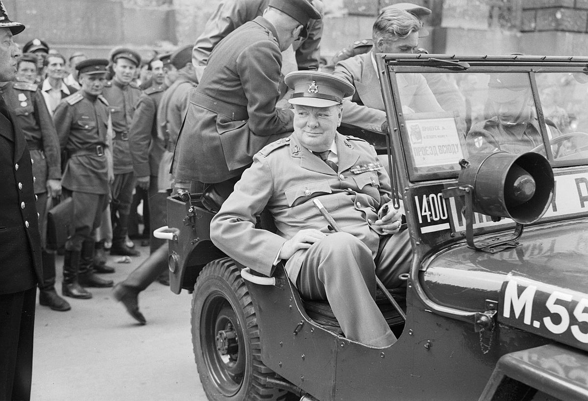 Winston Churchill speeches _in_a_jeep_outside_the_German_Reichstag_during_a_tour_of_the_ruined_city_of_Berlin,_16_July_1945._BU8950